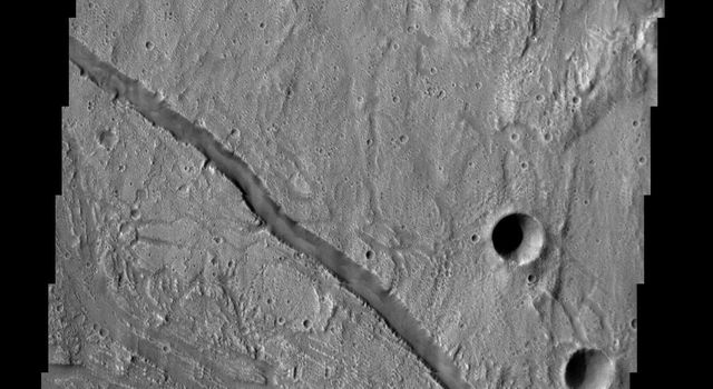 This crater and surrounding channels are part of Kasei Vallis on Mars as seen by NASA's 2001 Mars Odyssey spacecraft.