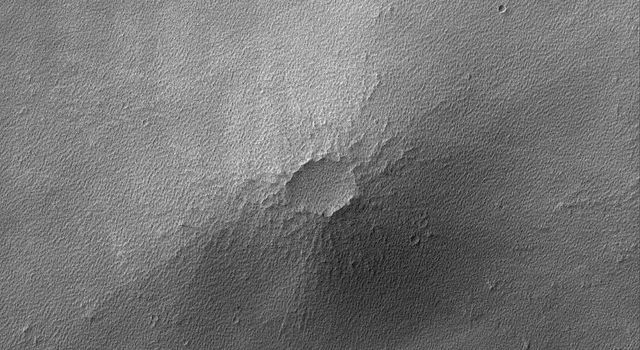 This image from NASA's Mars Global Surveyor shows a small volcano in the Syria Planum region of Mars. The lava flows that compose this small volcano are nearly hidden by a mantle of rough-textured, perhaps somewhat cemented, dust.