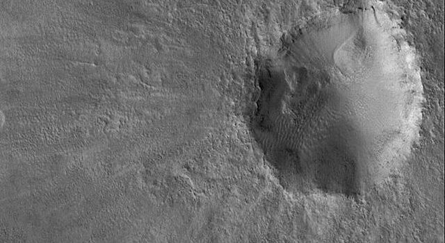 This image from NASA's Mars Global Surveyor shows an impact crater on the martian northern plains. This crater is roughly the size of the famous Meteor Crater in Arizona on the North American continent.