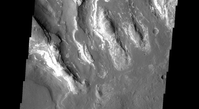This image is located in the Tyrrhena Terra region. The cause of the bright markings/material is unknown. It is possible that the formation of the channels are exposing a series of bright layered material on Mars as seen by NASA's Mars Odyssey spacecraft.