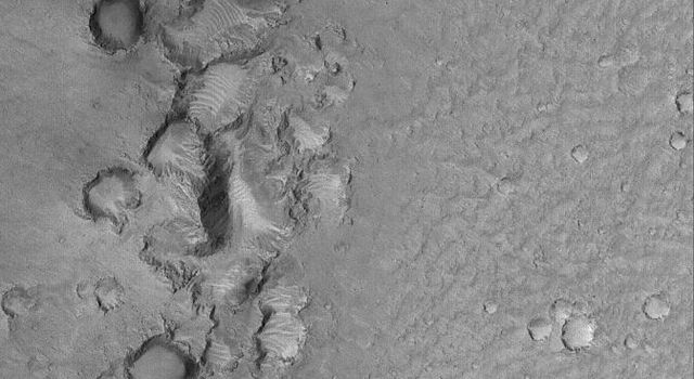 This image from NASA's Mars Global Surveyor shows a chain of clustered and battered craters. These were formed by secondary impact.