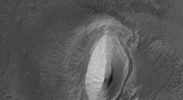 This image from NASA's Mars Global Surveyor shows a flow knob of light-toned, layered rock exposed by erosion in the Iani Chaos region of Mars.