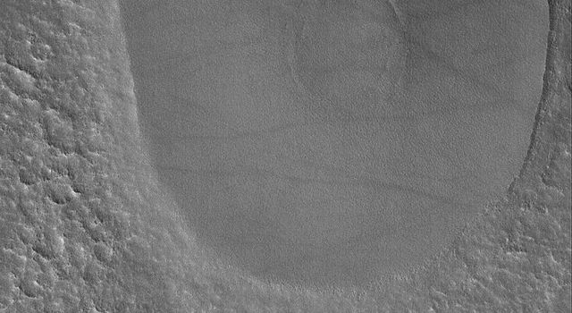 This image from NASA's Mars Global Surveyor shows two mesas on the northern plains of Mars. 'Mesa' is the Spanish word for 'table,' -- a very good description of the two elliptical features.
