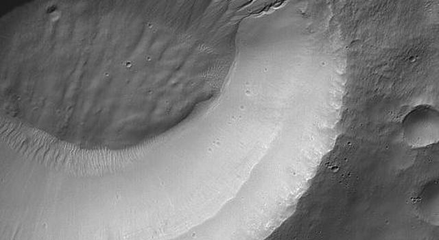 NASA's Mars Global Surveyor shows gullies all of which head at the same level on a south mid-latitude crater wall.
