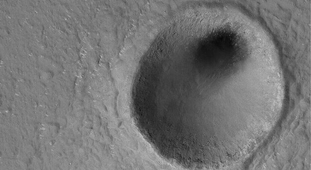 NASA's Mars Global Surveyor shows some a modest-sized meteor impact crater in the Elysium Planitia region of Mars. The dark spot inside the crater is, most likely, a patch of windblown sand and silt.