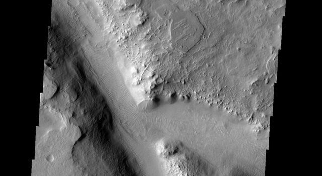 Sand dunes cover the floor of this channel in Terra Sabaea on Mars as seen by NASA's Mars Odyssey spacecraft.