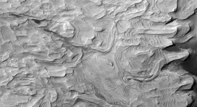NASA's Mars Global Surveyor shows light-toned, layered, sedimentary rocks in a crater in part of the Schiaparelli basin on Mars. The repetition of these horizontal layers suggests the sediments could have been deposited in an ancient crater lake.