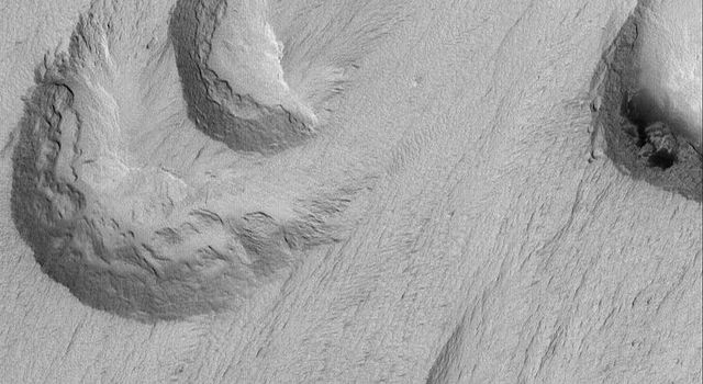 NASA's Mars Global Surveyor shows crescent-shaped, scooped-out hollows where wind has eroded the local bedrock in the Apollinaris Sulci region on Mars.