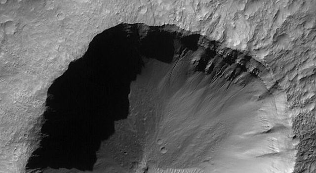 This image from NASA's Mars Global Surveyor shows rocks and gullies are visible in the northern walls of the crater. A small patch of large, windblown ripples cover part of the crater floor.