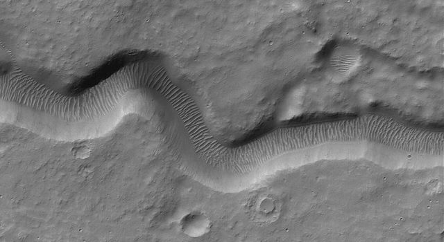 This image from NASA's Mars Global Surveyor shows narrow channel on the upper east flank of the martian volcano, Hadriaca Patera. Located on a volcano, this channel was likely formed by lava, perhaps as a lava tube at which the thin roof later collapsed.