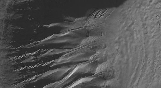 This image from NASA's Mars Global Surveyor shows gullies and cracked and stressed gully apron deposits in a south mid-latitude crater. Gullies can also be seen in the deep shadow on the north wall of the crater.