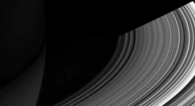 The image was taken in visible light with NASA's Cassini spacecraft wide-angle camera on Dec. 15, 2006. Both luminous and translucent, the C ring sweeps out of the darkness of Saturn's shadow and obscures the planet at lower left.