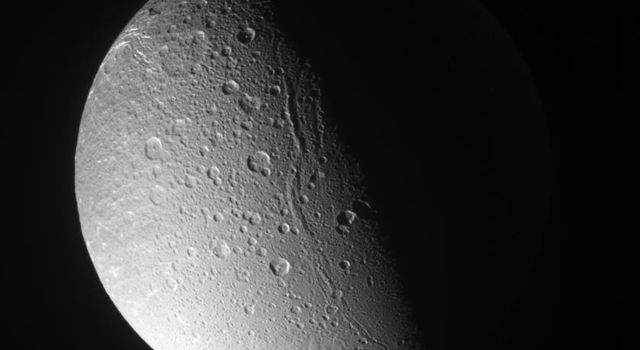Canyons and mountain peaks snake along the terminator on the crater-covered, icy moon Dione. A line of mountain ridges above center casts shadows toward the east as seen by NASA's Cassini spacecraft.