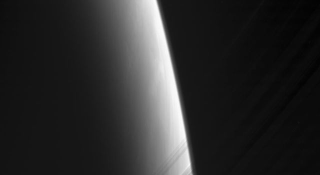 NASA's Cassini spacecraft looks toward daybreak on Saturn through the delicate strands of the C ring. Some structure and contrast is visible in the clouds far below.