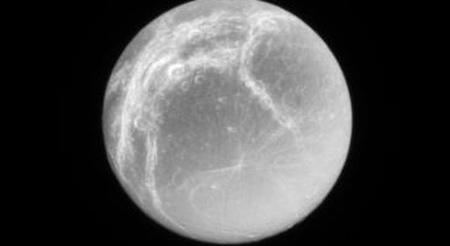 Bright icy fractures, or linea, cover the trailing hemisphere of Saturn's moon, Dione, in this image captured by NASA's Cassini spacecraft on Feb. 3, 2007.