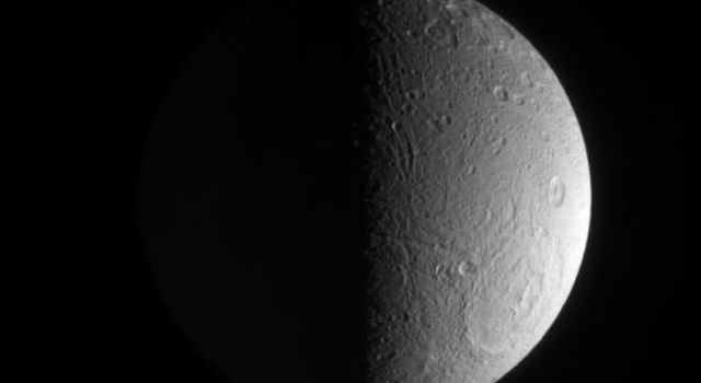 Grooves and deep craters adorn terrain at high southern latitudes on Saturn's moon, Dione, in this image taken by NASA's Cassini spacecraft on March 23, 2007.