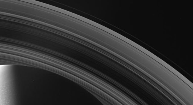NASA's Cassini spacecraft looks across Saturn's cloud-dotted north and shadowed pole, and out across the lanes of ice that compose its rings.