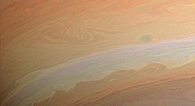 Whorls, streamers and eddies in hues of orange, yellow, and tan play in the banded atmosphere of the gas giant, Saturn. This image was taken with NASA's Cassini spacecraft's wide-angle camera.