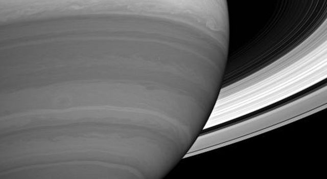Storms and cloud bands emerge from beneath Saturn's obscuring hazes in this infrared view from NASA's Cassini spacecraft.