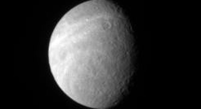 Wispy markings reach out across Rhea's surface from its trailing hemisphere. The bright markings appear to be fractures, like those found on Dione
