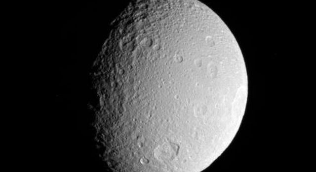 NASA's Cassini spacecraft surveys the battered surface of Saturn's icy moon Tethys. The great impact basin straddling the terminator is itself overprinted by many smaller impact sites.