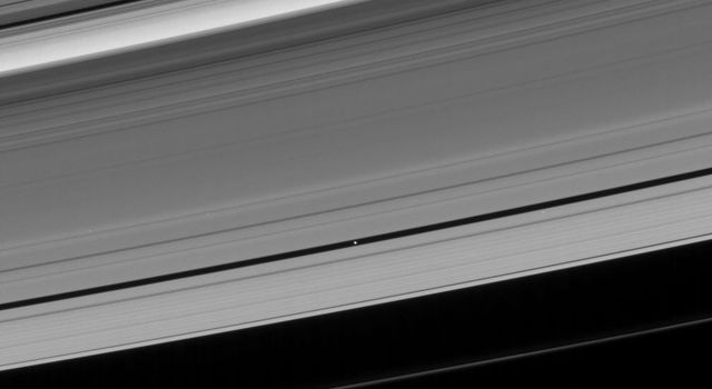 NASA's Cassini spacecraft looks toward the unilluminated side of Saturn's rings to spy on the moon Pan as it cruises through the Encke Gap.