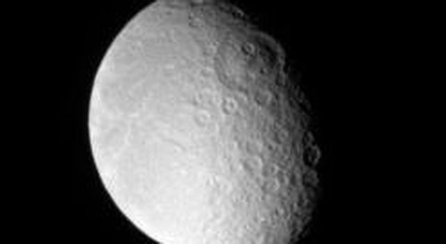 Rhea sports an immense impact scar on its leading hemisphere, like several other major Saturnian moons. The impact basin, seen above center on the day-night dividing line, or terminator, is named Tirawa