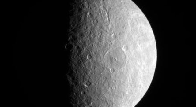 Large and medium-sized impact basins on Rhea's trailing hemisphere are thrown into sharp relief by the grazing rays of the Sun. This image was taken in visible light with NASA's Cassini spacecraft's narrow-angle camera.