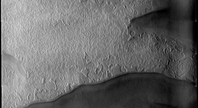 This image from NASA's Mars Odyssey spacecraft shows Mars' south polar cap, collected at the start of southern spring. The low sun angle highlights the different surface textures.
