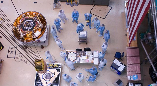 Spacecraft specialists huddle to discuss the critical lift of NASA's Phoenix Mars Lander into a thermal vacuum chamber.