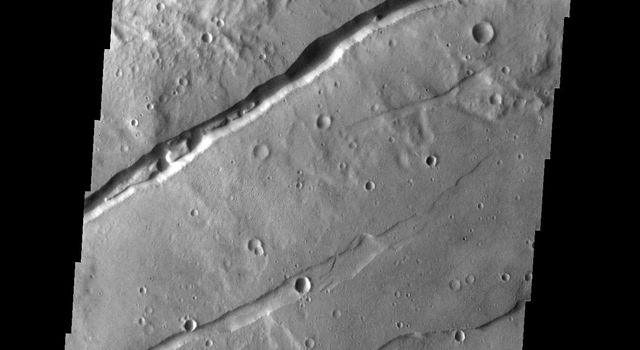 This image from NASA's Mars Odyssey spacecraft shows two sets of fractures on Mars, part of Sirenum Fossae. Several graben (downdroped blocks bounded by faults) occur between the main fracture systems.