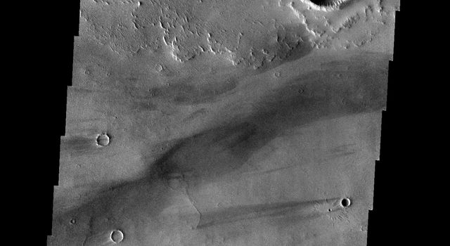 This image from NASA's Mars Odyssey spacecraft shows a strip of ground in the Daedalia Planum region of the giant volcanic province of Tharsis. The lava flows come from the Arsia Mons volcano on Mars.