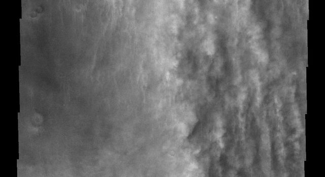 This image from NASA's Mars Odyssey spacecraft shows vertical features that look like long puffy streamers on Mars which are actually clouds at the margin of a large dust storm.