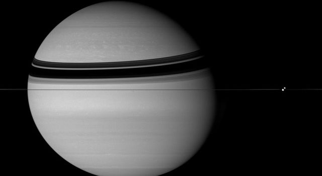 Dione and Tethys appear on opposite sides of the rings slide past each other in this stately portrait of Saturn taken by NASA's Cassini spacecraft.