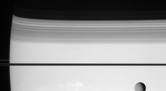 NASA's Cassini spacecraft puts the enormous distances in the Saturn system in perspective with this view of Rhea and Prometheus. This view looks toward the unilluminated side of the rings from less than a degree above the ringplane.