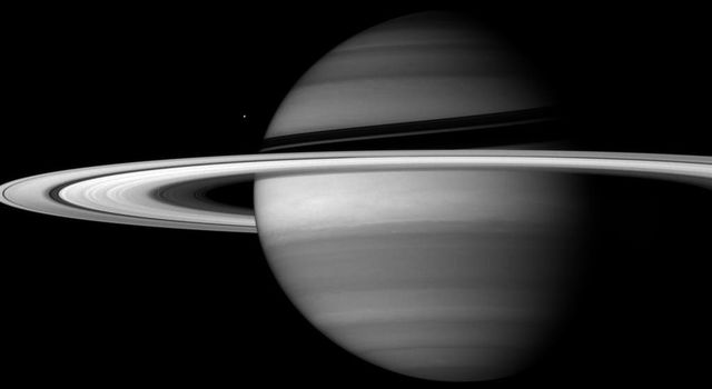 Saturn's incredible rings dwarf its moons in sheer scale. But all of their material, if compacted into a single body, would make a moon smaller than Enceladus, captured by NASA's Cassini spacecraft next to the planet's banded globe.