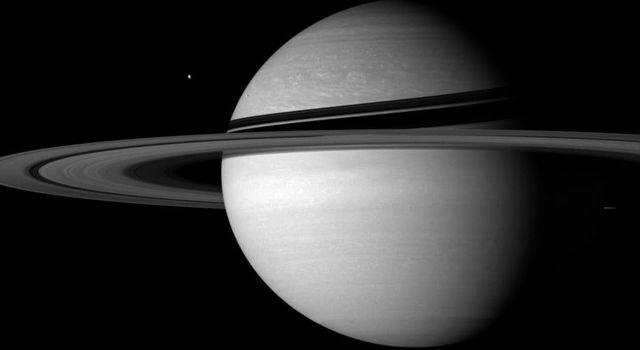 Icy sentinels Tethys and Enceladus stand guard on Saturn's doorstep, defying the distant Sun in this image captured by NASA's Cassini spacecraft on Sept. 20, 2007.