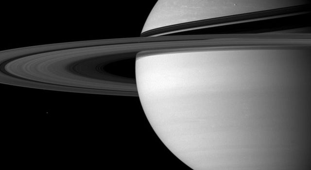NASA's Cassini spacecraft returns another dazzling postcard from its journey with this view of cloud-streaked Saturn and two of its moons, Enceladus and Mimas. This image was taken on Sept. 25, 2007.