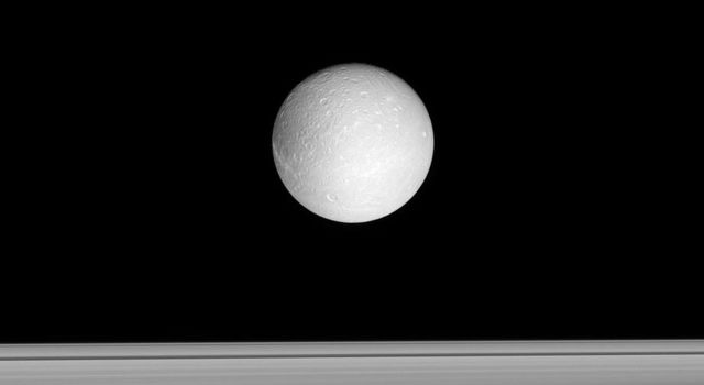Dione floats past, with Saturn's rings beyond. This image captured by NASA's Cassini spacecraft looks toward the anti-Saturn side of Dione (1,126 kilometers, or 700 miles across).
