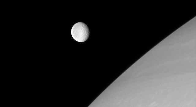 Rhea is frozen in this image from NASA's Cassini spacecraft, captured just before it glided in front of Saturn's northern hemisphere. The wispy streaks on Rhea's trailing side are partly visible in the west.