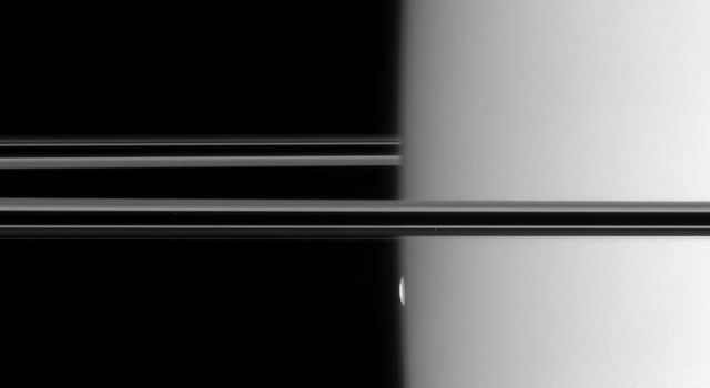 NASA's Cassini spacecraft watches a thin, bright sliver emerge from the hazy limb of Saturn. In one minute, the sliver ballooned into the full disk of Mimas in this image taken on Oct. 26, 2007.
