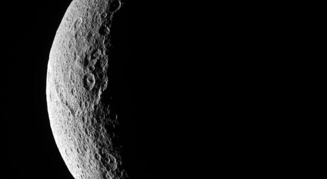 The low illumination angle near the terminator makes visible the steep topography of craters on Rhea's battered surface. This image was taken in visible light with NASA's Cassini spacecraft's narrow-angle camera on Nov. 16, 2007.