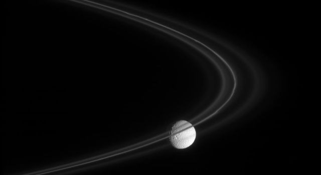 NASA's Cassini spacecraft peers through the fine, smoke-sized ice particles of Saturn's F ring toward the cratered face of Mimas in this captured on Nov. 18, 2007.