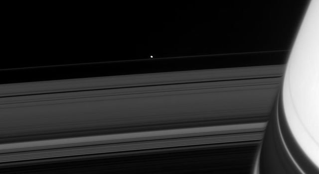Across the darkened expanse of Saturn's rings, NASA's Cassini spacecraft spied one of the F-ring shepherd moons, Pandora, in 2008.