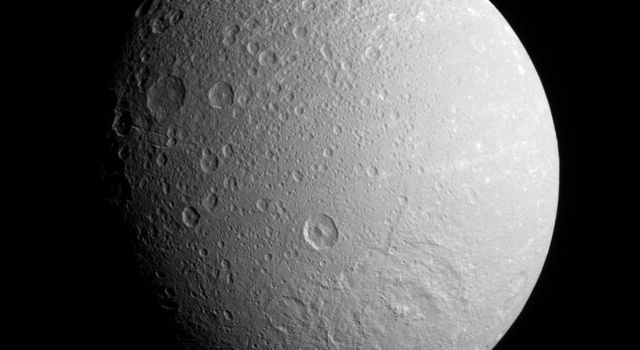 NASA's Cassini spacecraft surveys the southern hemisphere on Dione's anti-Saturn side, spying a broad impact basin near bottom. Most of the medium-sized craters visible here have pointed central peaks.