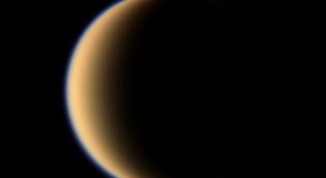Titan's hazy orange globe hangs before the Cassini spacecraft, partly illuminated -- a world with many mysteries yet to be uncovered.