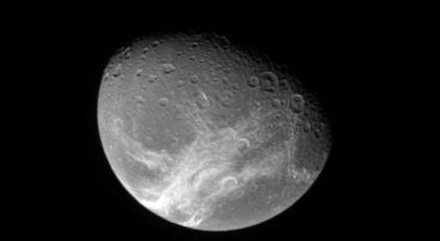 NASA's Cassini spacecraft looks down from high latitude over Dione and the system of wispy fractures that coats the moon's trailing side.
