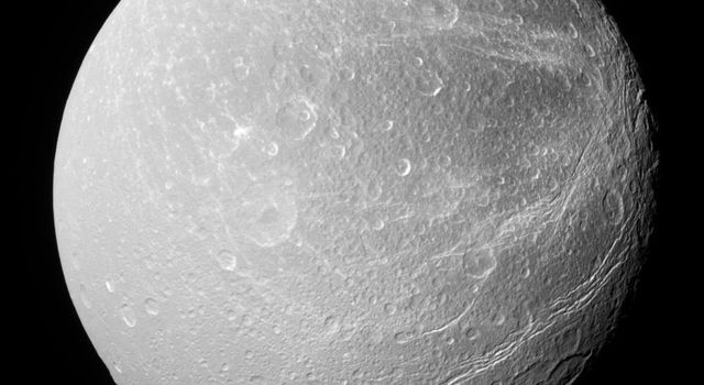 This southerly view of Saturn's moon Dione captured by NASA's Cassini spacecraft shows enormous canyons extending from mid-latitudes on the trailing hemisphere, at right, to the moon's south polar region.