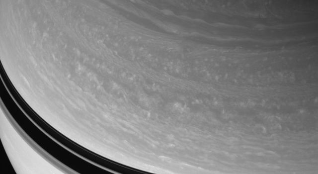 NASA's Cassini spacecraft observes the swirling features in Saturn's northern cloud bands. Ring-cast shadows darken the planet's northern hemisphere at increasingly lower latitudes.