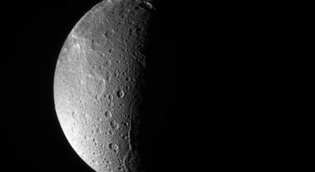 NASA's Cassini spacecraft looks down, almost directly at the north pole of Saturn's moon, Dione. The feature just left of the terminator at bottom is Janiculum Dorsa, a long, roughly north-south trending ridge.
